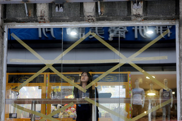 A woman stands behind taped window glasses in Taipei