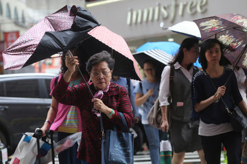People brave strong winds while crossing a street in Taipei