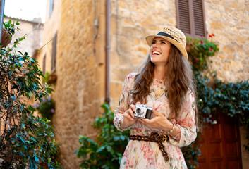 tourist woman with retro film photo camera having excursion