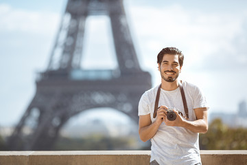 Paris Eiffel Tower tourist with camera taking pictures in front of the Eiffel tower, Paris, France. Young professional photographer handsome man in casual clothes outdoors in Europe.