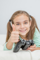 Happy little girl playing video games and showing thumbs up