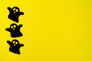 Holiday decorations for Halloween. Three black paper ghosts on a yellow background, top view.