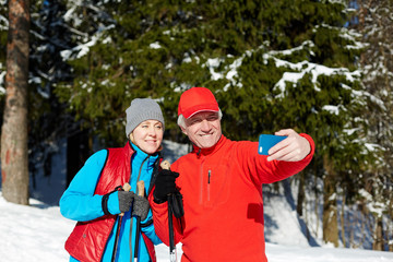 Happy seniors in winter activewear making selfie on smartphone during skiing training in the forest