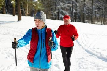 Mature female in activewear moving on skies on snowdrift while training with her husband on winter day