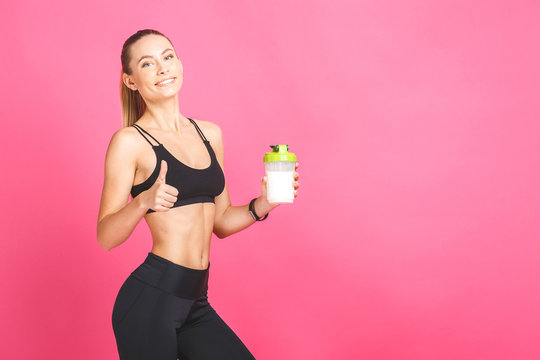 Athletic young woman with protein shake bottle. Isolated on pink background. Thumbs up.