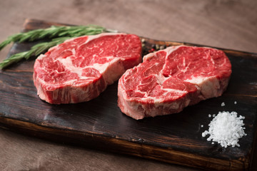 Printed roller blinds Steakhouse Two fresh raw rib-eye steak on wooden Board on wooden background with salt, pepper and rosmary in a rustic style