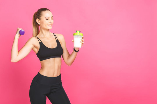 Portrait of athletic young woman with protein shake bottle and dumbells. Fitness concept isolated on pink background.