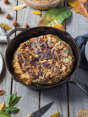 Delicious tortilla in frying pan on table