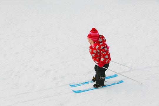 little girl learning to ski in winter