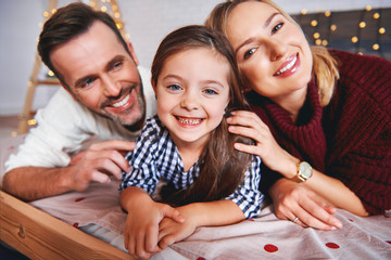 Portrait of family lying in bed at christmas time