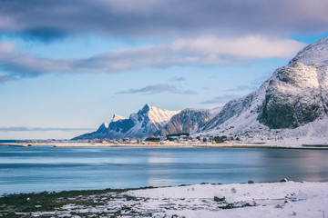 Lofoten Islands in winter. Beautiful daytime landscape with snowy rocky mountains, blue cloudy sky and small village on the sea coast, Northern Norway