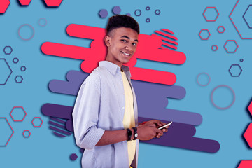 Beaming boy. Handsome beaming mulatto boy smiling after reading positive text message from friend while being in front of graphic ground