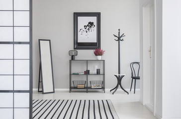 Map in black frame on the grey wall of corridor with mirror, shelf, hanger and hair, real photo