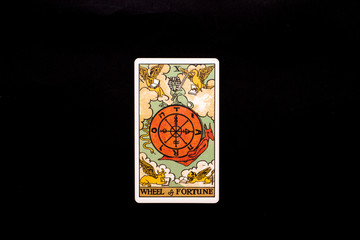 An individual major arcana tarot card isolated on black background. Wheel of fortune.