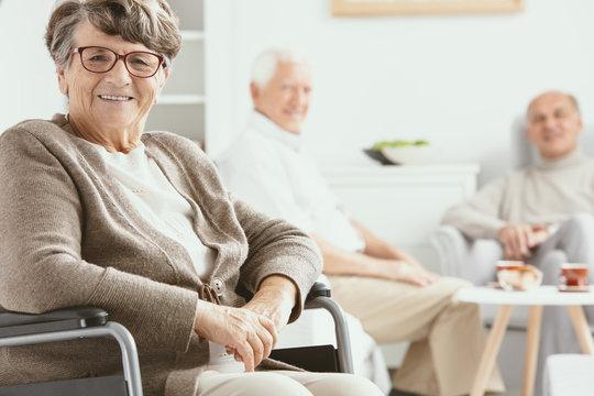 Happy paralyzed senior woman on wheelchair in the nursing house