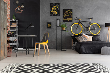 Chair at desk and patterned carpet in grey teenager's room interior with posters and bike. Real photo
