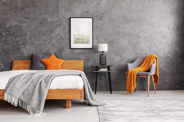 Grey and orange accents in simple and elegant bedroom with king size bed and painting on the empty concrete wall, real photo
