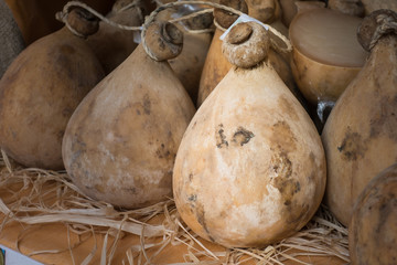 Many forms of caciocavallo cheese dop sale in Italian market.