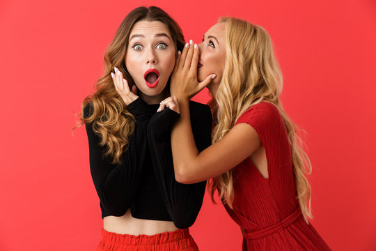 Amazing shocked young friends women standing isolated over red background.