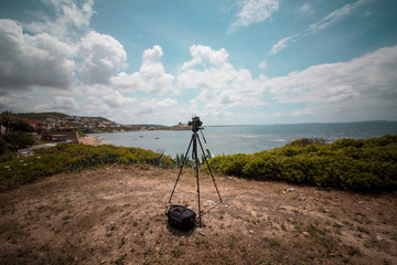 Camera and tripod shooting the sea and the beautiful coast of Sardinia, in Italy.
