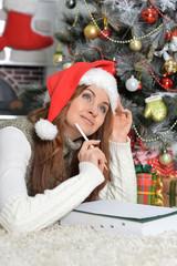 Portrait of girl in Santa hat writing letter