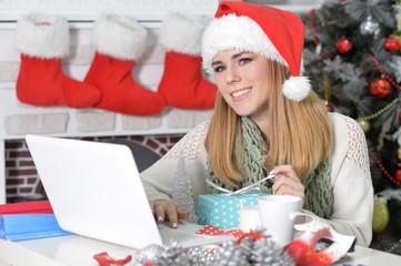 Portrait of woman using laptop preparing for Christmas