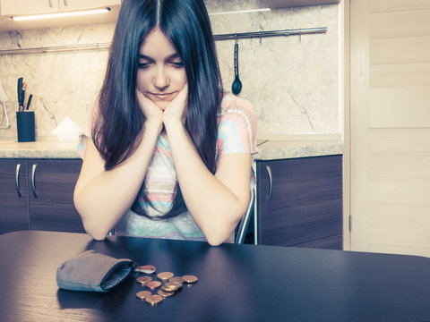 Concept of financial problems, a young disappointed woman with long dark hair, sits next to an old empty wallet with several coins on the table.