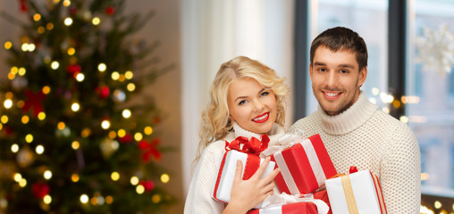 holidays and people concept - happy couple with gifts at home over christmas tree lights background