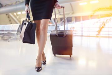 Geschäftsfrau mit Rollkoffer am Flughafen
