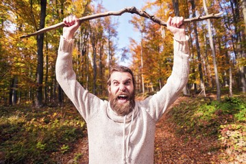 Young man in autumn forest shouting and holding wood branch