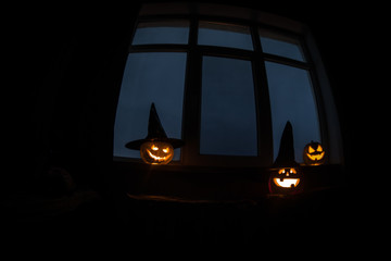 Scary Halloween pumpkin in the mystical house window at night or halloween pumpkin in night on room with blue window. Symbol of halloween in window.