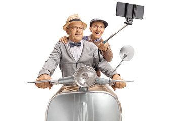 Two elderly gentlemen taking a selfie on a vintage scooter