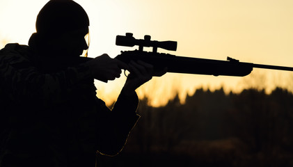 silhouette of an arrow with a rifle and a sight, on the hunt