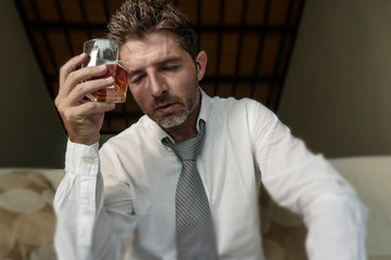 young attractive sad and desperate drunk addict businessman at home sofa couch drinking holding whiskey glass feeling depressed in alcohol addiction alcoholism problem and depression
