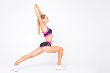 Great progress. Young beautiful woman in sportswear doing stretching isolated over white. Full photo.