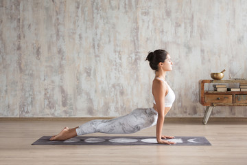 Young indian girl doing yoga fitness exercise indoor. Wellness concept. Calmness and relax. Yogi Instructor doing Urdhva mukha shvanasana exercise, upward facing dog pose, working out, home interior