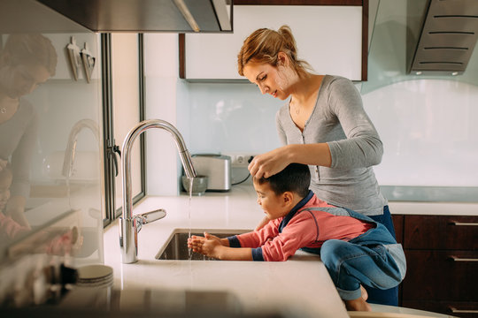 Caring mother and kid wash hands in a sink