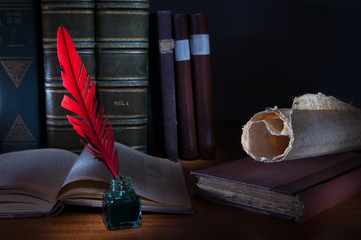 Red quill pen and a rolled papyrus sheet on a wooden table with old books