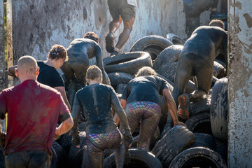 Athletes climbing over car tires at an obstacle course race