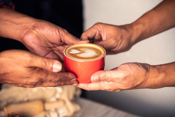 Barista's hands are delivering coffee to customers.