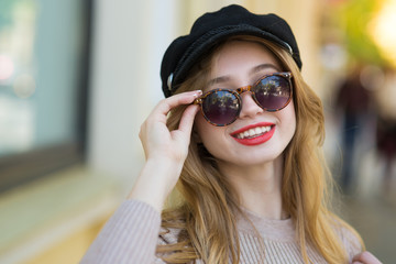 beautiful woman walks through city streets between building with sunglasses