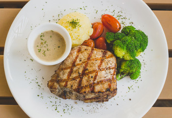 Top view of grilled pork steak with vegetable salad on a plate.