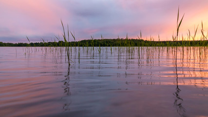 Reflected in the smooth water of the lake clouds at sunset. Colorful landscape, background blur