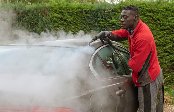 Man steam cleaning a luxury car on a home visiting valet service, England UK