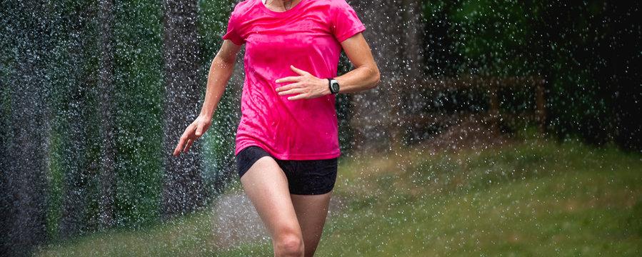 runner woman running under rain drops city marathon
