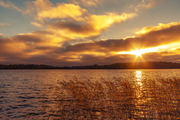 Sun's rays make their way through the clouds above the lake at sunset. Beautiful evening landscape background