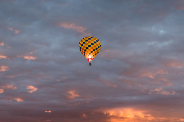 Colorful hot air balloon in yellow, orange, and dark blue colors glowing against a dramatic colorful sky and clouds at sunrise