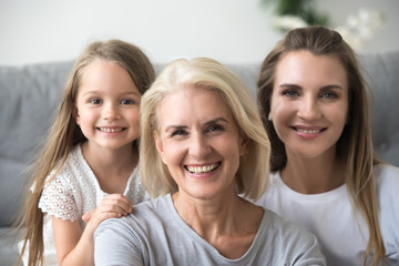 Portrait of smiling three generations of women look at camera posing for family picture at home, happy mother, daughter and grandmother in the middle embrace together showing love and support