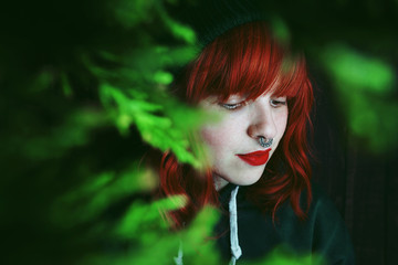 Young red haired woman between fir twigs