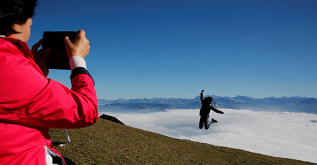 A tourist from South Korea takes a picture of her daughter jumping during sunny autumn weather near the peak of Mount Rigi